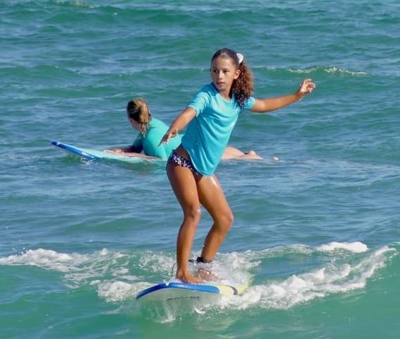 Jeune fille surfant une vague